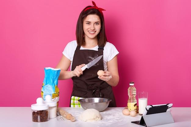 La mujer frena el huevo con un cuchillo, lo pone en un plato de harina, necesita más masa para preparar bollos cruzados calientes, lista para amasar, posando aislada sobre la pared rosa del estudio.