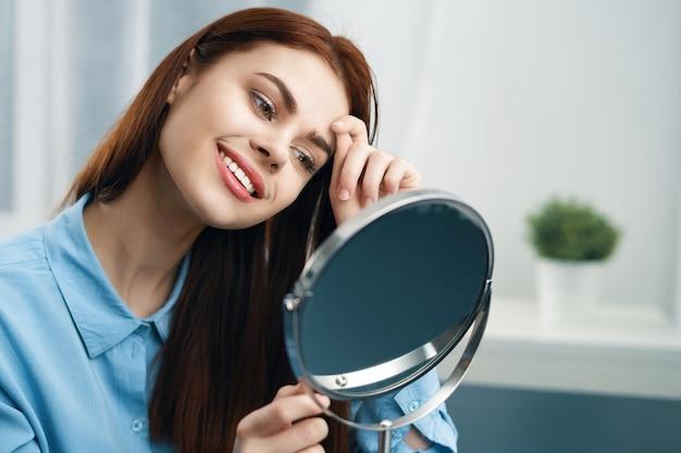 Mujer frente al espejo, cosméticos, cuidado del hogar.