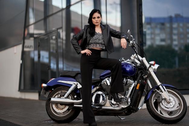 La mujer se para frente a una motocicleta frente a un edificio de vidrio en un estacionamiento cerca de un centro comercial.