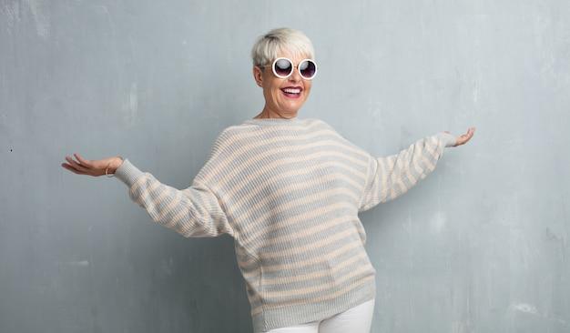 Mujer fresca mayor contra la pared del cemento del grunge.