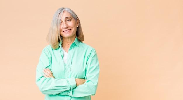 Mujer fresca de mediana edad que parece un triunfador feliz, orgulloso y satisfecho sonriendo con los brazos cruzados