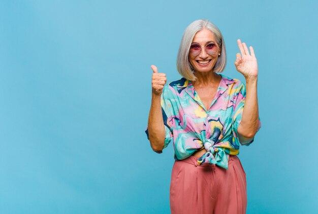 Mujer fresca de mediana edad que se siente feliz, asombrada, satisfecha y sorprendida, mostrando gestos de aprobación y pulgar hacia arriba, sonriendo