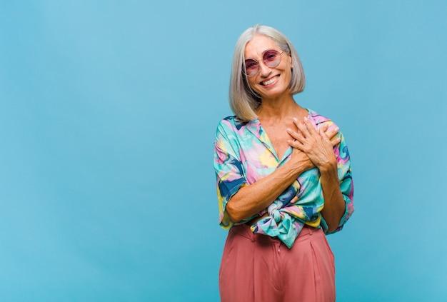 Mujer fresca de mediana edad que se siente romántica, feliz y enamorada, sonriendo alegremente y tomados de la mano cerca del corazón