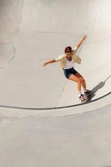 Mujer fresca de tiro completo divirtiéndose en patineta