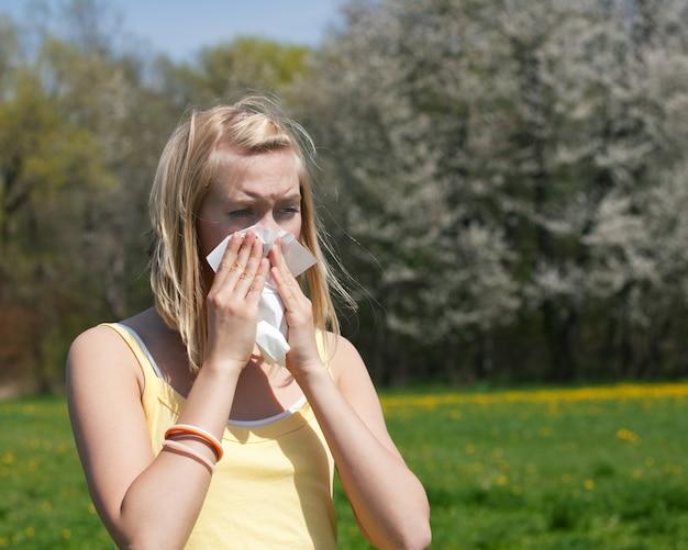 Mujer fría o enferma con alergia, soplando moco