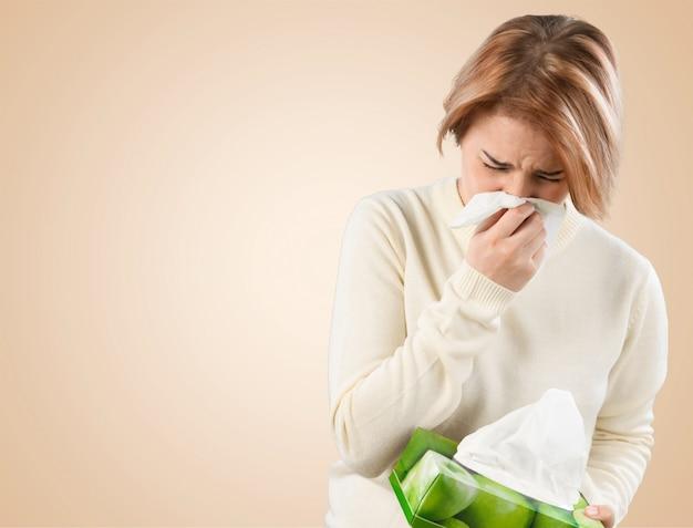 Mujer fría sosteniendo handkerchieif sonarse la nariz