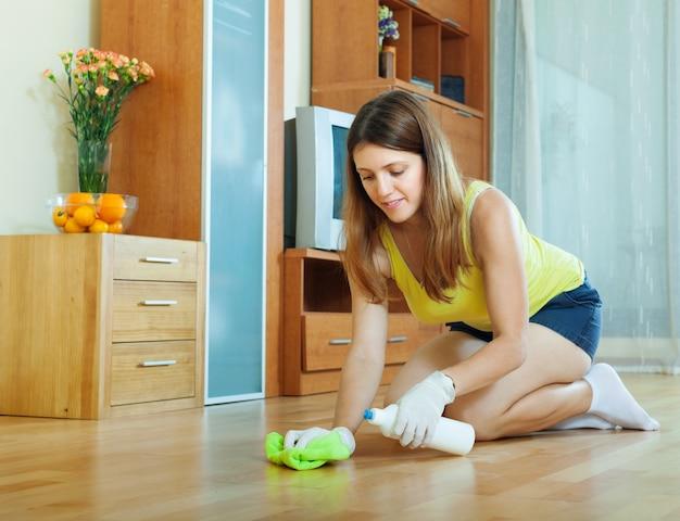 Mujer frotando piso de madera