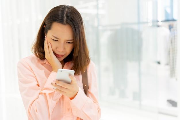 Mujer frunce el ceño con sentimientos serios mientras lee un comentario en las redes sociales para el concepto de cyber bully