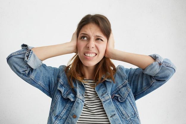 Mujer frustrada estresada tapándose los oídos