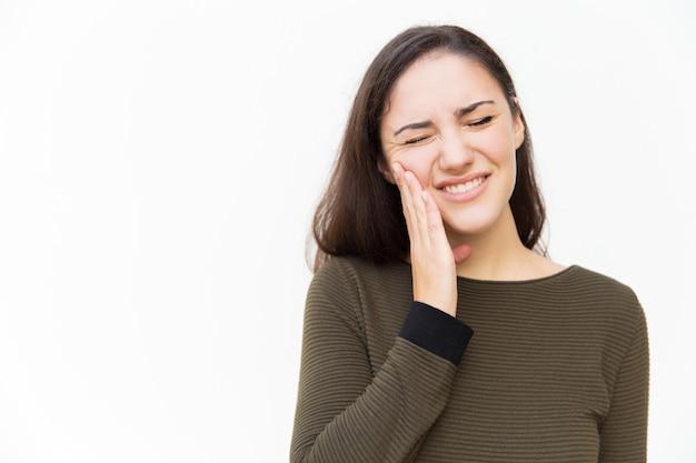Mujer frustrada con una mueca de dolor tocando la mejilla