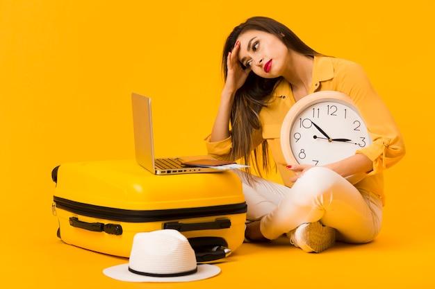 Mujer frustrada que sostiene el reloj y mirando el portátil encima del equipaje