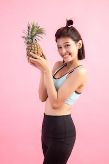 Mujer de la fruta de la piña que sonríe sana y alegre después del ejercicio para controlar el peso