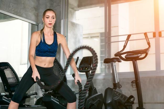 Mujer fuerte ejercicio con cuerda en entrenamiento funcional gimnasio.