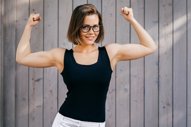Mujer fuerte fitness con cabello corto vestido casual, muestra sus bíceps al aire libre