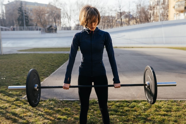 Mujer fuerte haciendo ejercicio con barra.