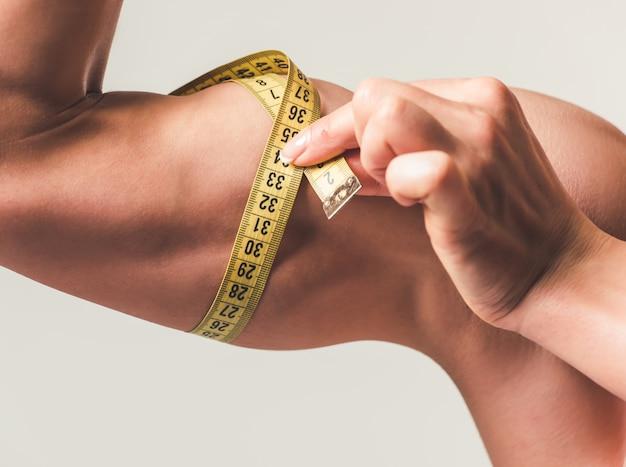Mujer fuerte midiendo sus bíceps.