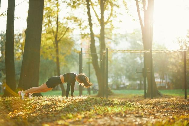 Mujer fuerte de pie en posición de plancha al aire libre