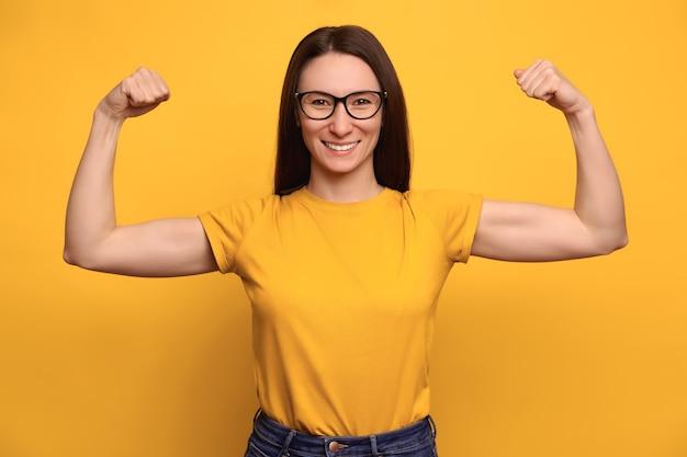 Mujer fuerte y poderosa con cabello oscuro, anteojos y sonrisa con dientes levanta los brazos y muestra los bíceps