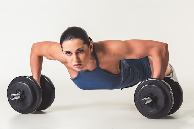 Mujer fuerte en ropa deportiva está trabajando con pesas