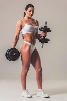 Mujer fuerte en ropa interior blanca con pesas.