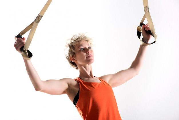 Mujer fuerte tirando de cables de fitness