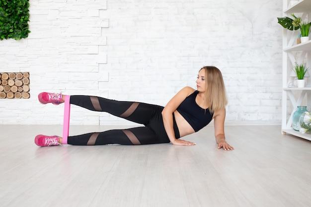 Mujer fuerte usando una banda de resistencia en su rutina de ejercicios.