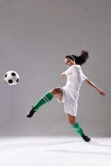 Mujer de fútbol pateando fútbol