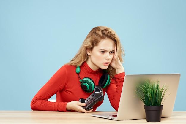 Mujer con gafas 3d juega un juego de computadora en consolas con joysticks en auriculares con una computadora portátil