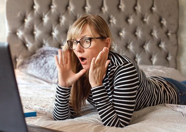 Mujer con gafas acostado en una cama mirando un portátil y preguntándose
