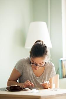 Mujer con gafas cuenta dinero en su teléfono