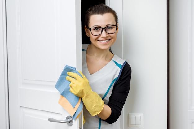 Mujer en gafas y delantal para limpiar guantes de goma con detergentes.
