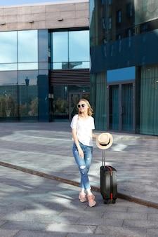 Mujer con gafas con equipaje de vacaciones cerca del edificio en verano