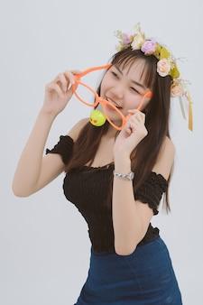 Mujer con gafas grandes, aislado en gris; retrato de muchacha asiática feliz y divertida en estudio.