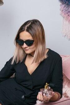 Mujer en gafas de moda de protección solar negro con perfume