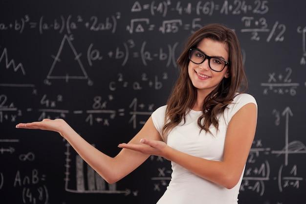 Mujer con gafas mostrando fórmulas matemáticas
