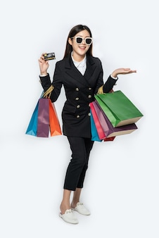 Mujer con gafas oscuras, ir de compras, llevar tarjetas de crédito y muchas bolsas