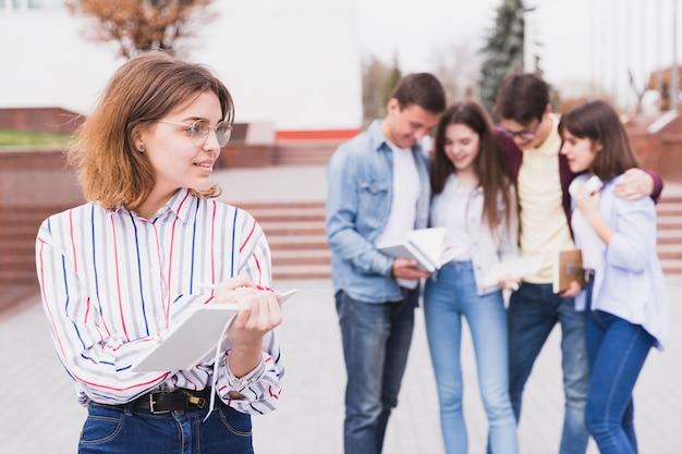 Mujer en gafas de pie y sosteniendo el cuaderno en las manos