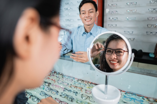 Una mujer con gafas y reflejándose en un vaso contra la pared de un escaparate de anteojos y un empleado en una clínica oftalmológica