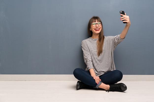 Mujer con gafas sentada en el suelo haciendo un selfie