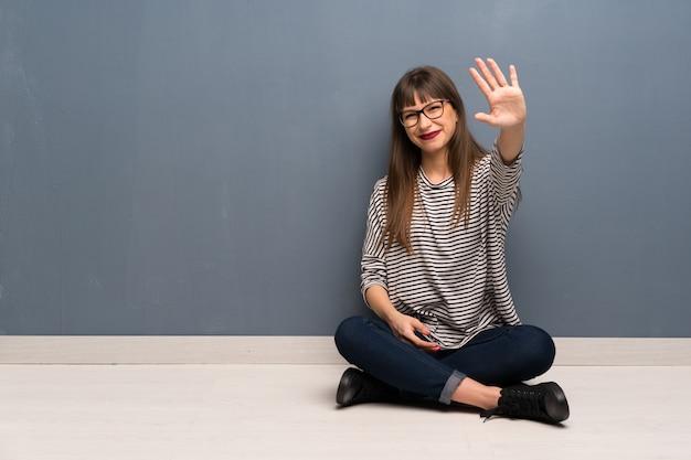 Mujer con gafas sentada en el suelo saludando con la mano con expresión feliz