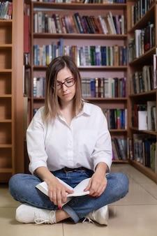 Una mujer con gafas se sienta en la biblioteca con libros.