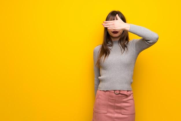 Mujer con gafas sobre pared amarilla cubriendo los ojos con las manos. no quiero ver algo