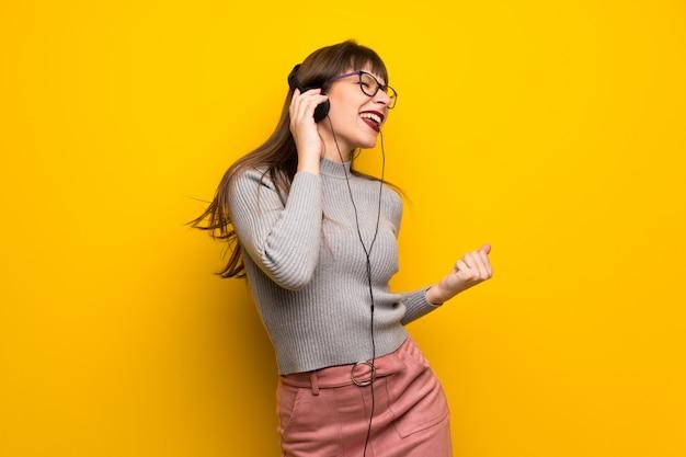 Mujer con gafas sobre pared amarilla escuchando música con auriculares y bailando