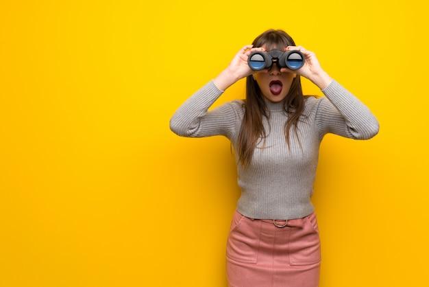 Mujer con gafas sobre pared amarilla y mirando en la distancia con binoculares