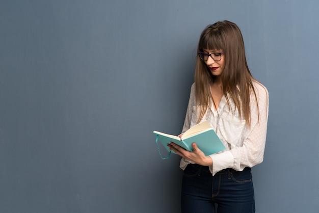 Mujer con gafas sobre pared azul sosteniendo un libro y disfrutando de la lectura