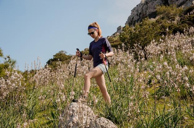 Mujer con gafas de sol caminando sobre las rocas con palos especiales