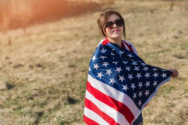 Mujer en gafas de sol envuelto en bandera americana mirando a cámara