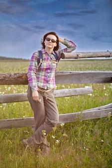 Mujer con gafas de sol se inclinó contra el seto de madera en la pradera para el pastoreo de ganado, en un día soleado de verano.