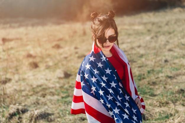 Mujer en gafas de sol lanzando bandera estadounidense sobre