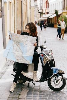 La mujer en gafas de sol originales se sienta en la vespa con el mapa turístico